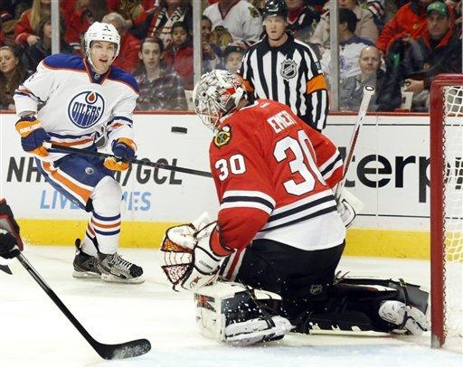 Chicago Blackhawks goalie Ray Emery makes a chest save on a shot by Edmonton Oilers left wing Taylor Hall, background, during the first period of an NHL hockey game Sunday, March 10, 2013 in Chicago. (AP Photo/Charles Rex Arbogast)