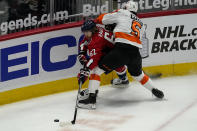 Washington Capitals left wing Carl Hagelin (62) passes the puck as he pinned by Philadelphia Flyers defenseman Philippe Myers (5) during the first period of an NHL hockey game, Friday, May 7, 2021, in Washington. (AP Photo/Alex Brandon)