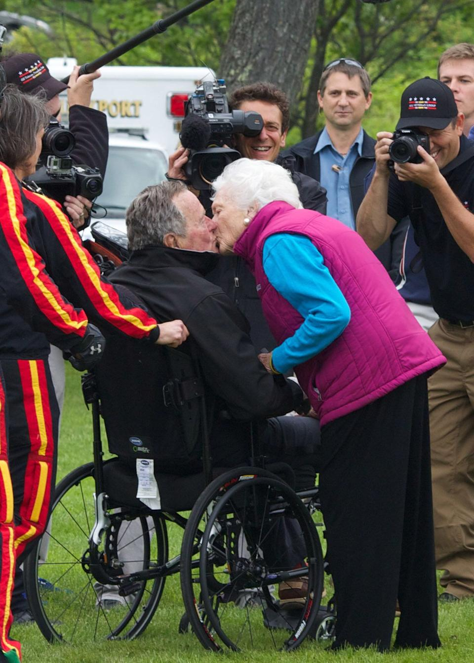 Barbara Bush greets her husband with a kiss after his successful skydive down to St. Anne's Episcopal Church on June 12, 2014, in Kennebunkport, Maine.