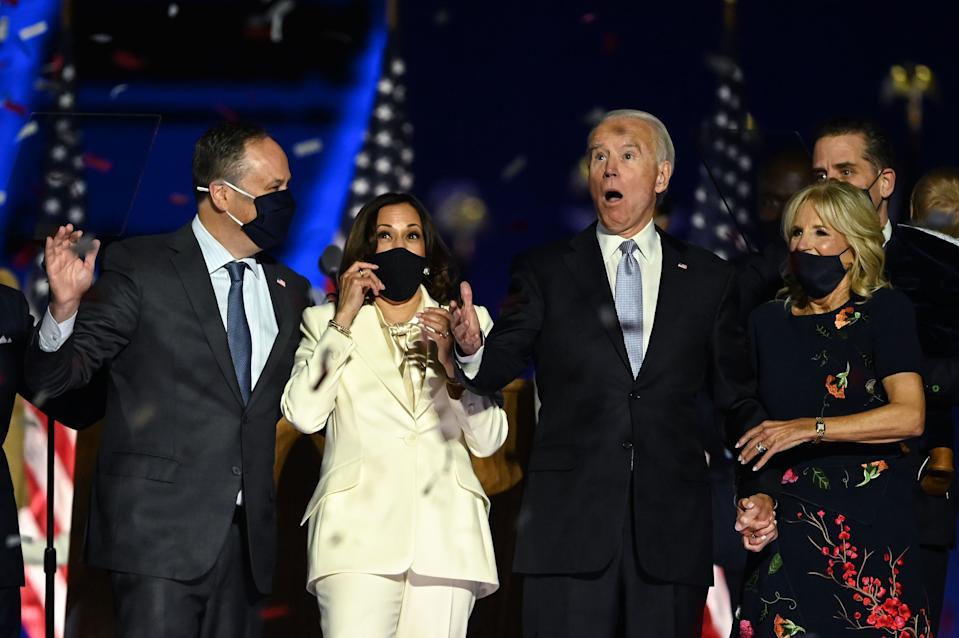 TOPSHOT - US President-elect Joe Biden (R) and Vice President-elect Kamala Harris (2nd L) react as confetti falls, with Jill Biden (R) and Douglas Emhoff, after delivering remarks in Wilmington, Delaware, on November 7, 2020, after being declared the winners of the presidential election. (Photo by Jim WATSON / AFP) (Photo by JIM WATSON/AFP via Getty Images)