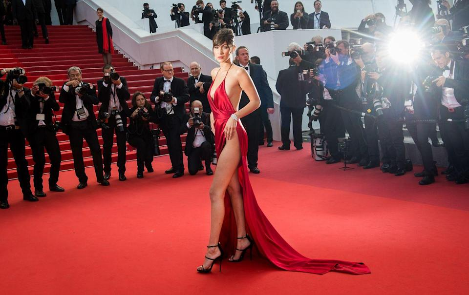 """<p>Bella Hadid is known for her head-turning red carpet looks, and she certainly gained a lot of attention in this red silk Alexandre Vauthier Couture gown, which featured a plunging neckline, low back and hip-high split. """"It's important to push boundaries and over the years I've done that,"""" she explained to us <a href=""""https://www.harpersbazaar.com/uk/fashion/fashion-news/a20679502/bella-hadid-interview-cannes-royals/"""" rel=""""nofollow noopener"""" target=""""_blank"""" data-ylk=""""slk:later in an interview in Cannes"""" class=""""link rapid-noclick-resp"""">later in an interview in Cannes</a>. """"I like to do whatever makes me feel good and a lot of the time that is pushing the boundaries."""" </p>"""