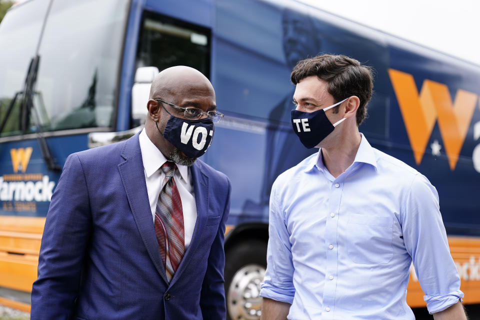 "Democratic candidate for Senate Jon Ossoff, right, and Democratic candidate for Senate Raphael G. Warnock, left, arrive before they speak to a crowd during a ""Get Out the Early Vote"" event on Oct. 27, 2020, in Jonesboro, Ga. (Brynn Anderson/AP)"