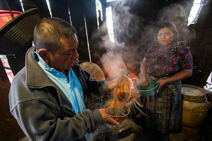 Maria Elvira Ramos, right, serves her husband Francisco Sical coffee in traditional Mayan bowl in early March 2020. Her outdoor kitchen is flanked with timber. Sical said he promised her a kitchen of cement block with money he would make working in the U.S., a dream that he gave up in summer 2019.