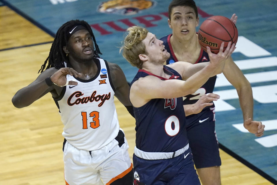 Liberty's Drake Dobbs shoots past Oklahoma State guard Isaac Likekele (13) during the second half of a first round NCAA college basketball game Friday, March 19, 2021, at the Indiana Farmers Coliseum in Indianapolis.Oklahoma State won 69-60. (AP Photo/Charles Rex Arbogast)