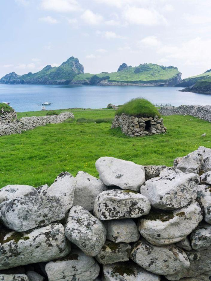 """<p>While this was once a lush island occupied by many people, in the 1930s it was evacuated because of the <a href=""""http://www.atlasobscura.com/articles/ghost-islands"""" rel=""""nofollow noopener"""" target=""""_blank"""" data-ylk=""""slk:threat of starvation and harsh weather"""" class=""""link rapid-noclick-resp"""">threat of starvation and harsh weather</a>. Now, abandoned stone structures are speckled across the fields.</p>"""