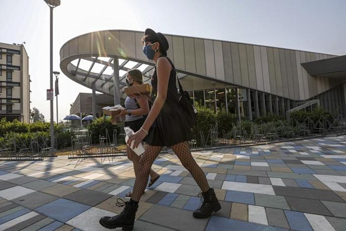 """Students walk back to their dorms with takeout breakfast from the Cal State Fullerton dining facility a few days before the start of classes last month. <span class=""""copyright"""">(Irfan Khan / Los Angeles Times)</span>"""