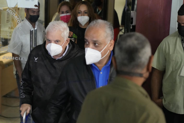 Panama's former President Ricardo Martinelli, center left, exits a court using a walker at the end of the first day of his trial, in Panama City, Wednesday, July 21, 2021. Martinelli is charged with political espionage during his administration, the same case for which he was acquitted in 2018. (AP Photo/Arnulfo Franco)