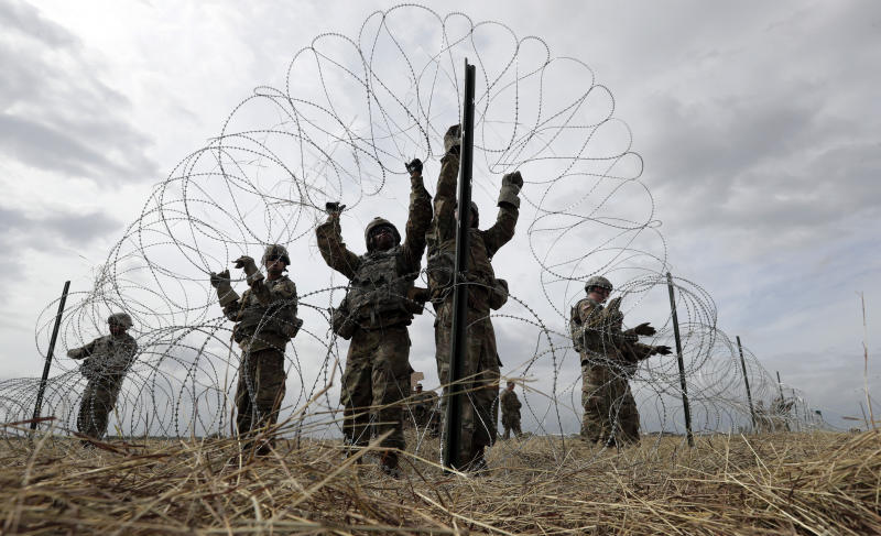 Members of a U.S Army engineering brigade place concertina wire around an encampment