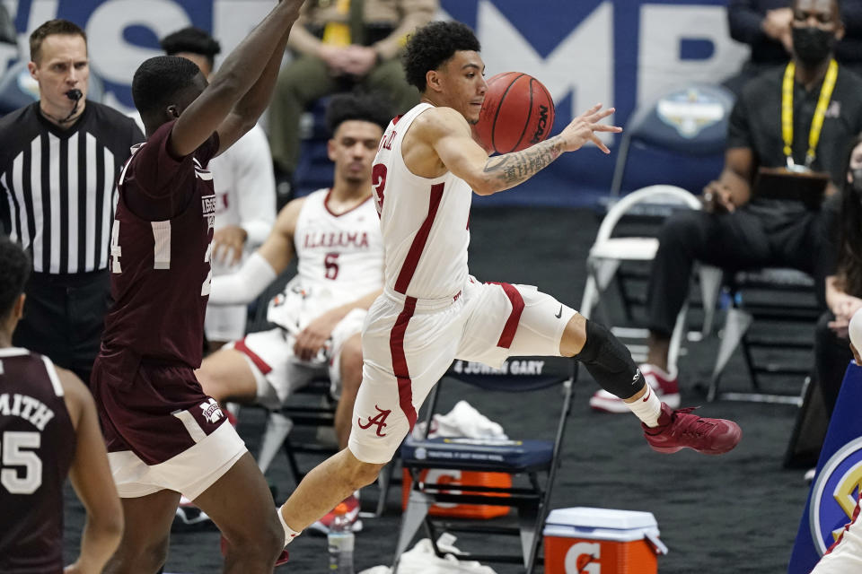 Alabama's Jahvon Quinerly, center, passes the ball in the second half of an NCAA college basketball game against Mississippi State in the Southeastern Conference Tournament Friday, March 12, 2021, in Nashville, Tenn. (AP Photo/Mark Humphrey)