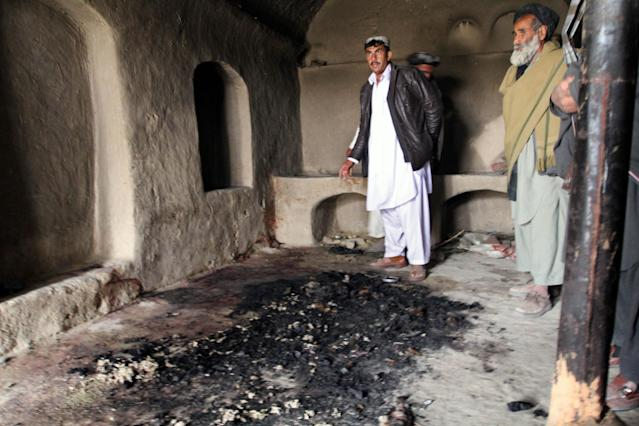 FILE - In this Sunday, March 11, 2012 file photo, men stand next to blood stains and charred remains inside a home where witnesses say Afghans were killed by a U.S. soldier in Panjwai, Kandahar province south of Kabul, Afghanistan. U.S. Army Staff Sgt. Robert Bales was charged on Friday, March 23, 2012 with 17 counts of premeditated murder, a capital offense that could lead to the death penalty in the massacre of Afghan civilians, the U.S. military said. (AP Photo/Allauddin Khan, File)