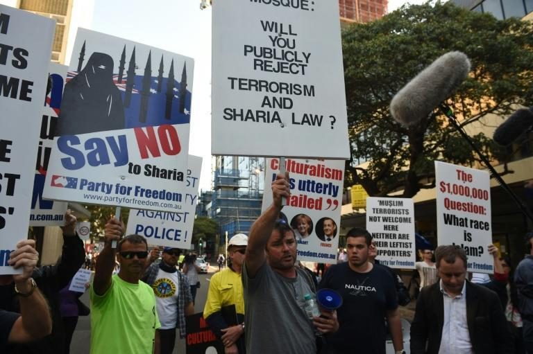 Anti-Muslim protesters hold up placards and shout slogans outside the Parramatta Mosque in Sydney on October 9, 2015