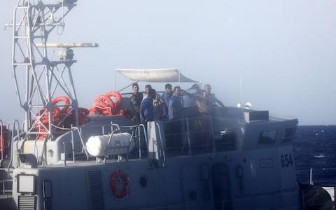 A Libyan coast guard officer aboard a vessel signals at former fishing trawler Golf Azzurro of the Proactiva Open Arms to move away from the area in the Western Mediterranean Sea