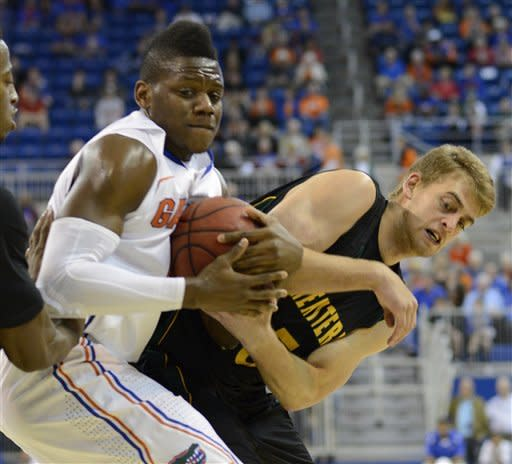 Florida's forward Will Yeguete, second from right, struggles to keep the ball as he struggles with Southeastern Louisiana forward Jan Petrovcic, right, during the first half of an NCAA college basketball game in Gainesville, Fla., Wednesday, Dec. 19, 2012. (AP Photo/Phil Sandlin)