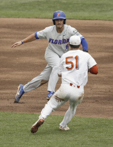 Florida's Jonathan India (6) is tagged out by Texas first baseman Jake McKenzie (51) in a rundown between second and third bases in the third inning of an NCAA College World Series baseball elimination game in Omaha, Neb., Tuesday, June 19, 2018. (AP Photo/Nati Harnik)