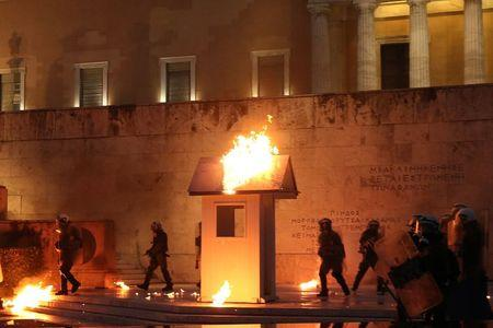 Riot police walk among flames by petrol bombs as a guard post of the Tomb of the Unknown Soldier burns during clashes outside the parliament building as Greek lawmakers vote on the latest round of austerity Greece has agreed with its lenders, in Athens, Greece, May 18, 2017. REUTERS/Costas Baltas