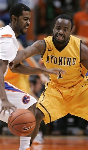 Boise State's Michael Thompson (1) tries to get past the reach of Wyoming's Derrious Gilmore during the first half of an NCAA college basketball game, Saturday, Feb. 9, 2013, in Boise, Idaho. (AP Photo/Matt Cilley)