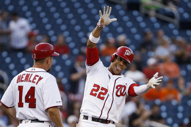 Washington Nationals' Juan Soto (22) celebrates his two-run triple with third base coach Bob Henley during the first inning of the team's baseball game against the Baltimore Orioles at Nationals Park on Wednesday, Aug. 28, 2019, in Washington. (AP Photo/Alex Brandon)