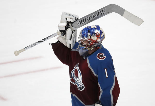 Colorado Avalanche goaltender Semyon Varlamov raises his stick in celebration as time runs out in the third period of an NHL hockey game against the Vancouver Canucks Monday, Feb. 26, 2018, in Denver. The Avalanche won 3-1. (AP Photo/David Zalubowski)