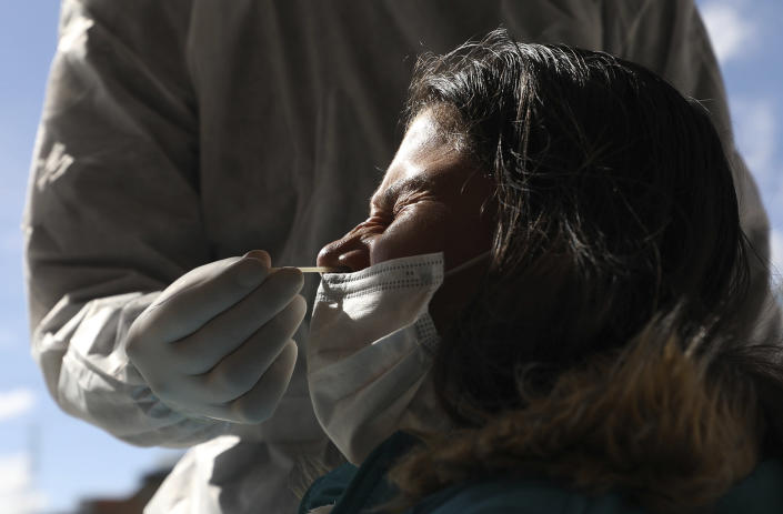 A woman grimaces as a healthcare worker collects a nasal swab sample to test for COVID-19, in Bogota, Colombia, Wednesday, Jan. 27, 2021. The Colombian government announced that the first shipment of new coronavirus vaccines will arrive in February. (AP Photo/Fernando Vergara)