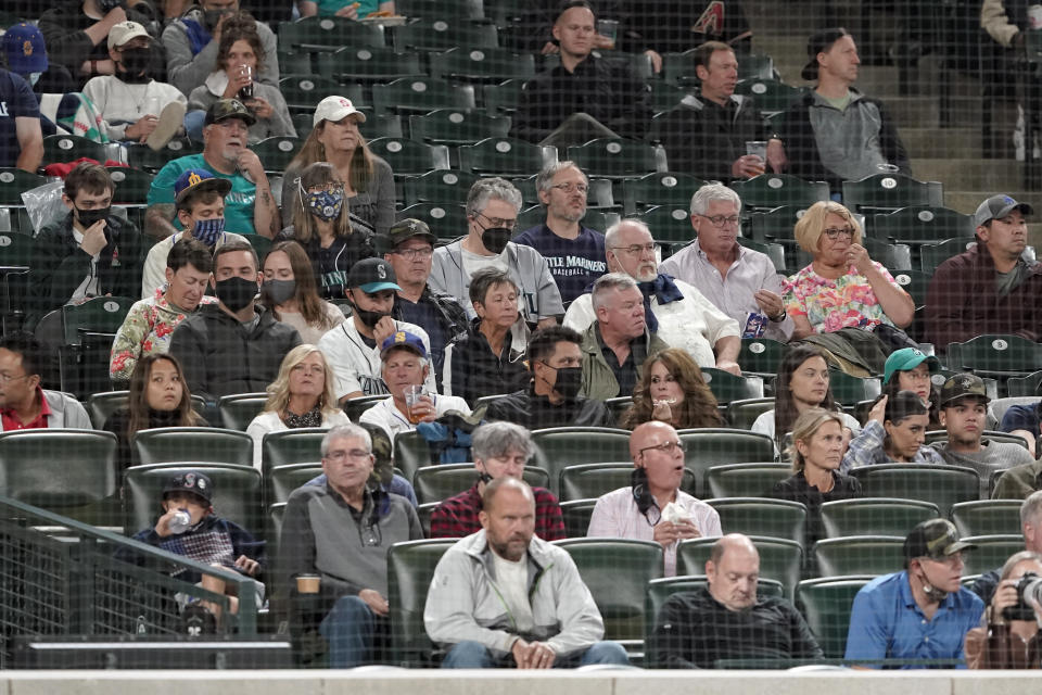 A few fans in the stands at T-Mobile Park wear masks against the spread of COVID-19 as they watch a baseball game between the Seattle Mariners and the Arizona Diamondbacks, Friday, Sept. 10, 2021, in Seattle. The game was the first home game for the Mariners since King County officials began requiring masks at all times (except when eating or drinking) for outdoor gatherings of more than 500 people. A similar statewide requirement goes into effect next week. (AP Photo/Ted S. Warren)