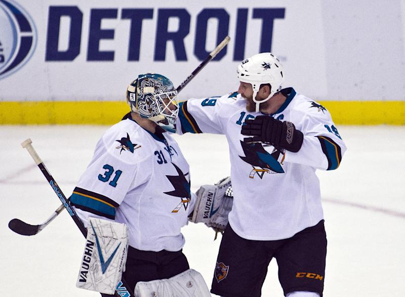 San Jose Sharks goalie Antti Niemi (31), of Finland, celebrates with captain Joe Thornton (19), Niemi blocked the game winning shootout shot after overtime in an NHL hockey game in Detroit, Mich., Monday, Oct. 21, 2013. San Jose won 1-0 on shootouts. (AP Photo/Tony Ding)