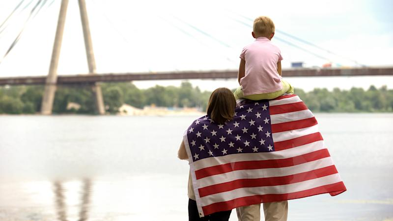 Back view of family wrapped in USA flag looking at bridge, independence day
