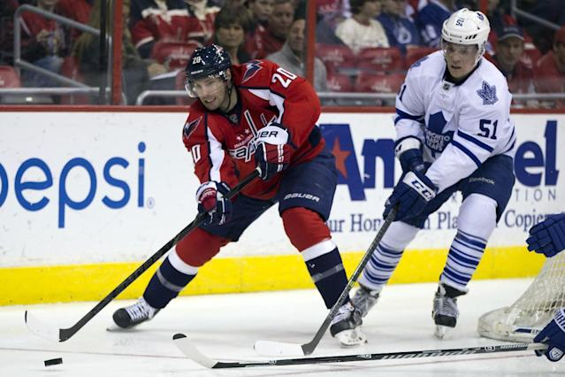 Toronto Maple Leafs defenseman Jake Gardiner (51) defends against Washington Capitals right wing Troy Brouwer (20) during the second period of an NHL hockey game on Sunday, March 16, 2014, in Washington. (AP Photo/ Evan Vucci)