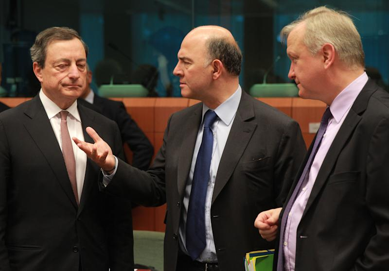 President of the European Central Bank Mario Draghi, left, listens at French Finance Minister Pierre Moscovici, second left, and European Commissioner for Economic and Monetary Affairs Olli Rehn, right, during the eurogroup ministerial meeting at the European Council building in Brussels, Monday March 10, 2014. (AP Photo/Yves Logghe)