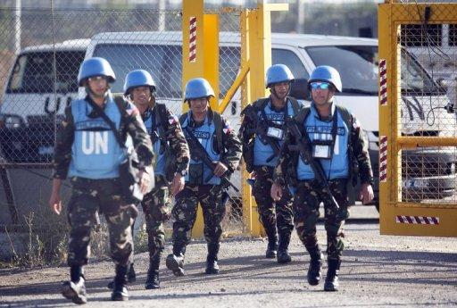 UN peacekeepers head for the Israeli annexed Golan Heights from the Quneitra crossing on June 12, 2013