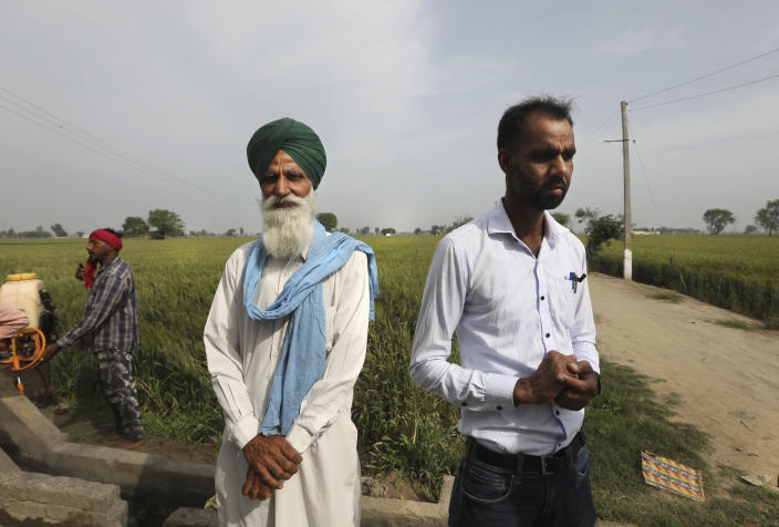 Indian farmer Bhupinder Singh, 62, center, with his son Swarn Singh, 32, stand near their field in Moga district of Indian state of Punjab, Saturday, March 13, 2021. India is home to a fifth of the world's population but has only 4% of the world's water. The country is the largest extractor of groundwater in the world, and 90% of it is used for agriculture. And nowhere is the water shortage more pronounced than in Punjab state, where the India encouraged the cultivation of wheat and rice in the 1960s and has since been buying the staples at fixed prices to shore up national reserves. (AP Photo/Manish Swarup)
