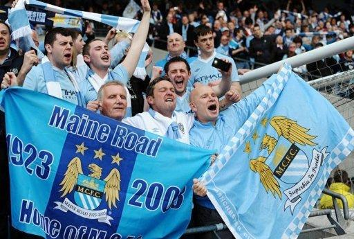 Manchester City's supporters celebrate after their team's 3-2 victory over Queens Park Rangers. Manchester City won the game 3-2 to secure their first title since 1968