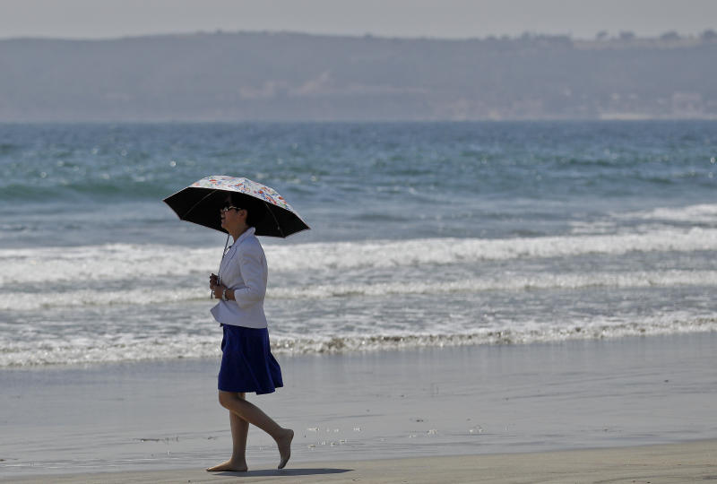 "In this May 22, 2012 photo, a woman walks barefoot along the Coronado Beach in Coronado, Calif. The Coronado Beach has been named America's best beach. Coronado Beach tops the 2012 list of Top 10 Beaches produced annually by coastal expert Stephen P. Leatherman, also known as ""Dr. Beach,"" director of Florida International University's Laboratory for Coastal Research. (AP Photo/Lenny Ignelzi)"