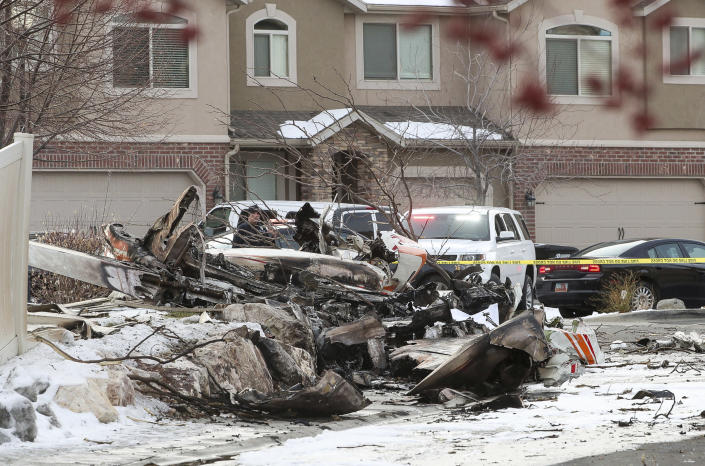 This photo shows debris from a small private plane that crashed in a residential area in Roy, Utah, Wednesday, Jan. 15, 2020. The small plane crashed Wednesday, killing the pilot as the aircraft narrowly avoided hitting any townhomes, authorities said. (Steve Griffin/The Deseret News via AP)