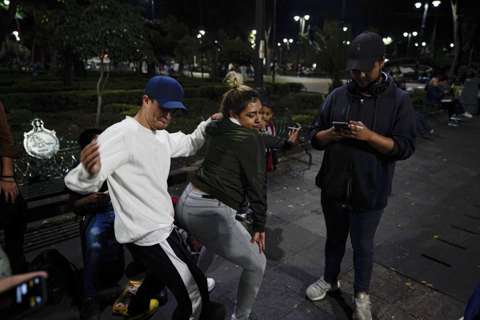 Youths dance during a rap performance at a plaza in the Coyoacan neighborhood of Mexico City, Friday, July 23, 2021. Hours after Mexico City authorities raised the alert level in the face of rising COVID-19 infections, many residents of the capital's trendy Coyoacan neighborhood crammed its center ignoring social distancing and forgoing masks. (AP Photo/Fernando Llano)