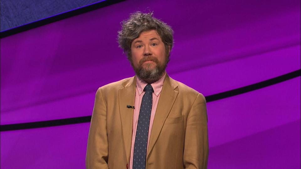 """<p>Austin Rogers' sarcastic banter with Alex Trebek earned him a special place in the hearts of <em>Jeopardy! </em>fans—as did his 12 game streak, which earned him $411,000. Owing to his upbeat demeanor and quirky sense of humor (some called it """"Krameresque""""), Rogers became a viral sensation during his winning streak. After his streak ended, Rogers <a href=""""https://www.cnbc.com/2020/01/07/jeopardy-champ-austin-rogers-won-400k-and-kept-his-bartending-job.html"""" rel=""""nofollow noopener"""" target=""""_blank"""" data-ylk=""""slk:bought"""" class=""""link rapid-noclick-resp"""">bought</a> a rare 1989 Honda Civic, traveled the world, and returned to his job as a New York City bartender. Today, Rogers is still bartending at The Gaf West, where he worked prior to <em>Jeopardy!</em>, as well as hosting trivia nights at other bars.</p>"""