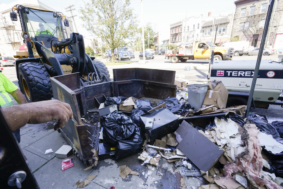 Village of Mamaroneck workers use a front loader to remove water logged items from left out on the sidewalk after remnants of Hurricane Ida inundated the community, Saturday, Sept. 4, 2021, in Mamaroneck, N.Y. More than four days after the hurricane blew ashore in Louisiana, Ida's rainy remains hit the Northeast with stunning fury on Wednesday and Thursday, submerging cars, swamping subway stations and basement apartments and drowning scores of people in five states. (AP Photo/Mary Altaffer)