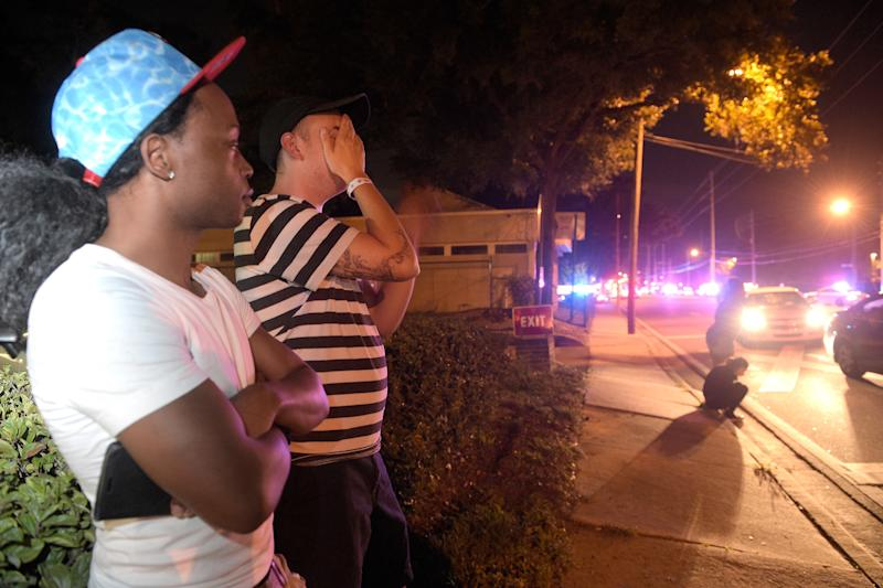 FILE - In this June 12, 2016, file photo, Jermaine Towns, left, and Brandon Shuford wait down the street from Pulse nightclub in Orlando, Fla., where a gunman opened fire, killing 49 people. In the five years since a gunman killed 20 children and six adults at the Sandy Hook elementary school in Newtown, Conn., the nation has witnessed even deadlier attacks, including the shooting at the Pulse nightclub and the Oct. 1, 2017, shooting in Las Vegas, where a man in a casino hotel gunned down 55 concertgoers on the ground below. (AP Photo/Phelan M. Ebenhack, File)