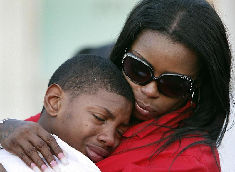 Teresa Carter, right, mother of Chavis Carter, comforts her other son Kizziah Carter on Monday, Aug. 20, 2012 following a prayer vigil held on the grounds of The National Civil Rights Museum in Memphis, Tenn., for Chavis Carter, who Jonesboro, Arkansas, police say committed suicide while handcuffed. (AP Photo/The Commercial Appeal, Stan Carroll)