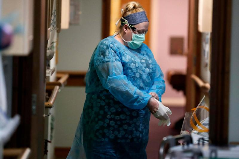 A nurse puts on PPE (personal protective equipment) at the Wren Hall care home in Nottingham (AP)