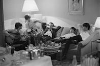 <p>John Lennon strums his guitar as the band relaxes in their Paris hotel room with their manager—because even the biggest rock stars in the world need their downtime.</p>