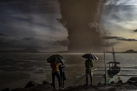 Residents look on as Taal Volcano erupts on January 12, 2020 in Talisay, Batangas province, Philippines - Credit: Ezra Acayan