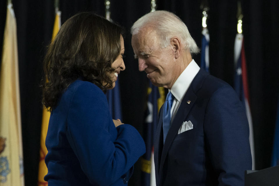 FILE - In this Aug. 12, 2020, file photo, Democratic presidential candidate former Vice President Joe Biden and his running mate Sen. Kamala Harris, D-Calif., pass each other as Harris moves to the podium to speak during a campaign event at Alexis Dupont High School in Wilmington, Del. Harris made history Saturday, Nov. 7, as the first Black woman elected as vice president of the United States, shattering barriers that have kept men — almost all of them white — entrenched at the highest levels of American politics for more than two centuries. (AP Photo/Carolyn Kaster, File)