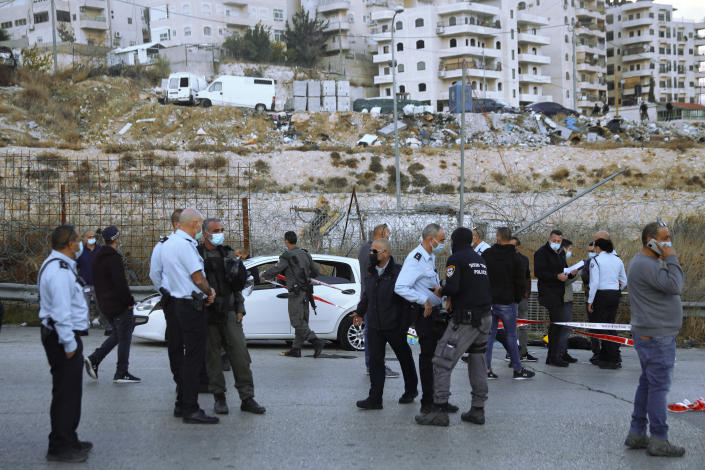 Israeli police inspect the scene of what they say was an attempted car-ramming attack at a West Bank checkpoint near Jerusalem, Wednesday, Nov. 25, 2020. Israeli forces shot and killed the Palestinian motorist who police said tried to ram his car into a soldier at the checkpoint. (AP Photo/Mahmoud Illean)