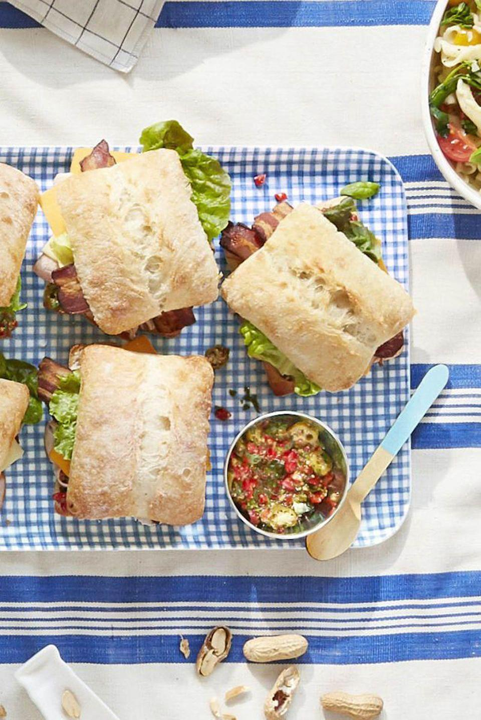 """<p>These sandwiches—filled with sharp cheddar cheese and turkey bacon—are the ideal size when you want a few bites but don't want to fill all the way up.</p><p><strong><a href=""""https://www.countryliving.com/food-drinks/recipes/a42460/pimiento-salad-club-sandwiches-recipe/?visibilityoverride"""" rel=""""nofollow noopener"""" target=""""_blank"""" data-ylk=""""slk:Get the recipe"""" class=""""link rapid-noclick-resp"""">Get the recipe</a>.</strong></p><p><a class=""""link rapid-noclick-resp"""" href=""""https://www.amazon.com/Classic-Gingham-Serving-Handles-Serveware/dp/B00ZDVHLZI/?tag=syn-yahoo-20&ascsubtag=%5Bartid%7C10050.g.3290%5Bsrc%7Cyahoo-us"""" rel=""""nofollow noopener"""" target=""""_blank"""" data-ylk=""""slk:SHOP TRAYS"""">SHOP TRAYS</a> </p>"""