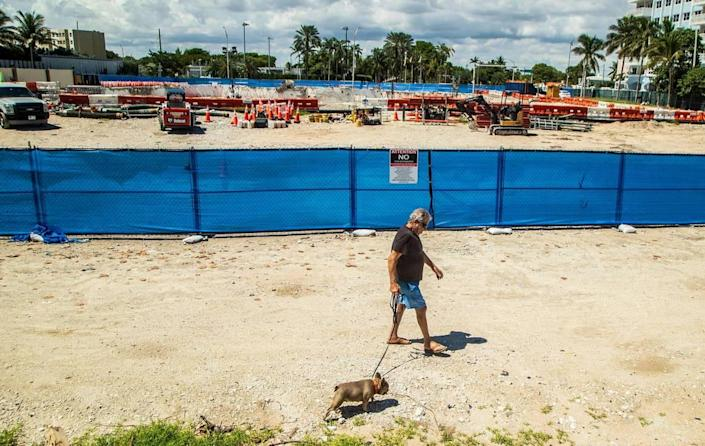 A man walks his dog near the Champlain Towers South property in Surfside, Florida, on Thursday, Sept. 23, 2021.