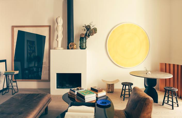 """<div class=""""caption""""> A wall displays part of Champsaur's art collection, including a Richard Serra lithograph to the left, and a yellow painting by Swiss artist Carmen Perrin. On the mantel is an anonymous plaster sculpture and a vase by French designer Eric Schmitt. The leather chair is from the Paris flea market, and the coffee table and dining table are both Champsaur designs for Pouenat Ferronnier. The diminutive bronze in the background is also a Champsaur design, this for Maison Intègre. </div>"""