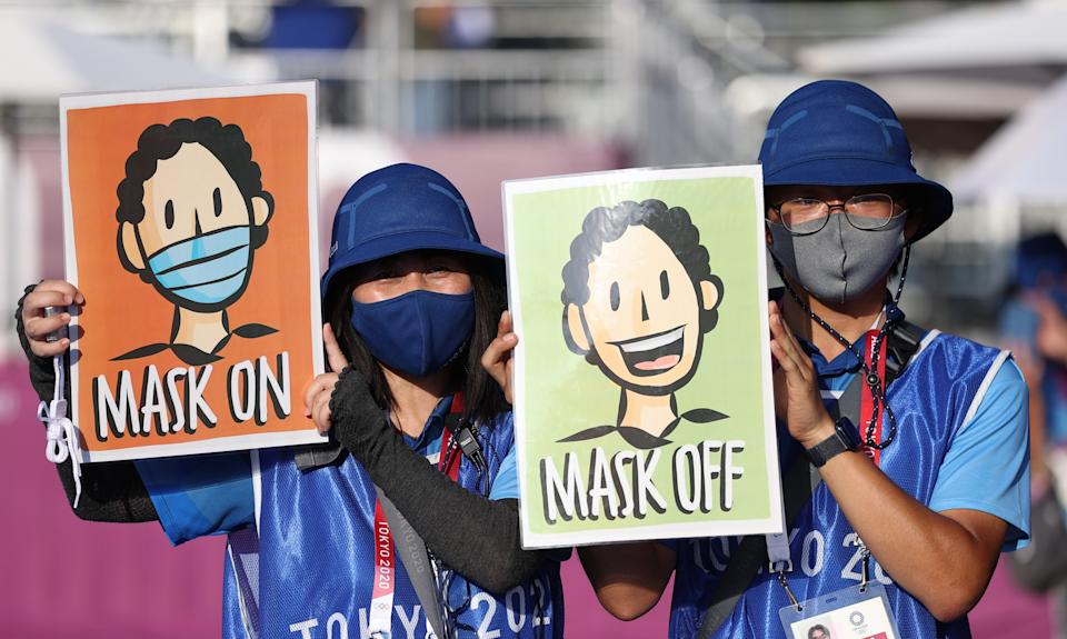 """<p>People hold posters with a message """"Mask on, Mask off"""" during the women's archery team qualification event at the 2020 Summer Olympic Games, at Yumenoshima Final Field. Sergei Bobylev/TASS (Photo by Sergei Bobylev\TASS via Getty Images)</p>"""