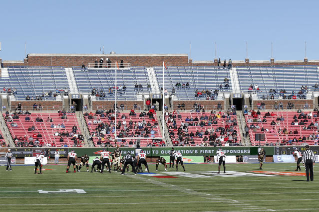FILE- This Dec. 30, 2019, file photo shows empty seats as Western Kentucky and Western Michigan line up for the snap during the second half of the NCAA First Responder Bowl college football game in Dallas. Bowls outside the College Football Playoff structure might excite only the most ardent fans of the participating teams, be played in half-empty stadiums and prompt howls about there being too many games. They aren't going away, though. There'll be three more next season, bringing the total number of bowls to 42. (AP Photo/Roger Steinman, File)
