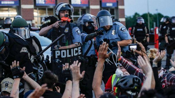 PHOTO: In this May 31, 2020, file photo, a police officer points a hand cannon at protesters who have been detained pending arrest on South Washington Street, in Minneapolis. (John Minchillo/AP, FILE)