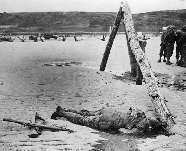 <p>A dead American soldier lies face down on a Normandy, France, beach following the 1944 D-Day invasion. (Photo: Three Lions/Getty Images) </p>